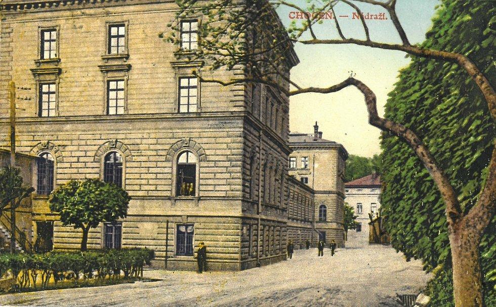 Dobová kolorovaná pohlednice, vpředu nádražní budova, vzadu bývalý hotel Spiegel