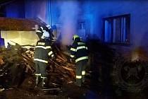 Oheň spálil uskladněné dřevo a poničil fasádu.
