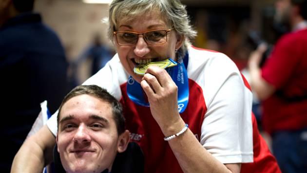 Tělesně postižený sportovec Adam Peška oslavuje se svou asistentkou i maminkou Ivanou montrealské zlato.