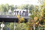 Policejní těžkooděnci odstrkávají z mostu fanoušky Hradce.