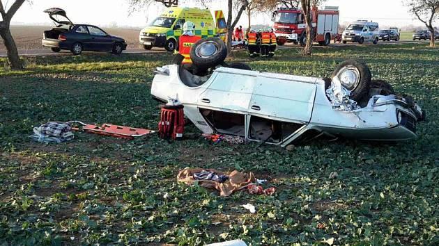 Automobil skončil po nehodě v poli a na střeše.