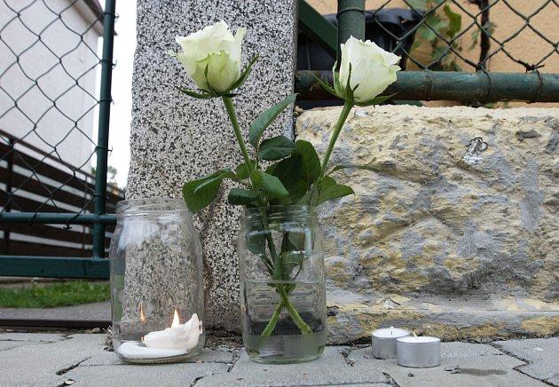 Květiny a svíčky před domem zavražděného dítěte.