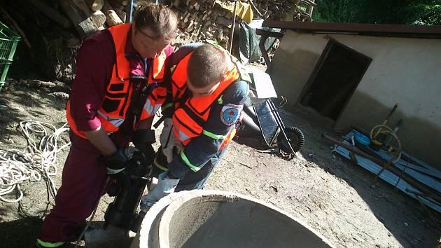 Dobrovolní hasiči z Lázní Bohdaneč pomáhají čistit studnu.