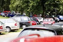Odvrácená strana sportu. Místo zámeckého parku obklopují tenisové kurty auta, zatímco městská parkoviště zejí prázdnotou
