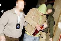 Policisté předvádějí zatčeného výrobce pervitinu k výslechu