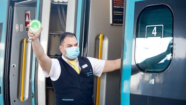 Průvodčí Českých drah chrání sebe i cestující rouškou kvůli šíření koronaviru a nařízení karantény vládou.