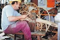 ZBYNĚK ŠIMEK opracovává  dřevěný rám pro drezínu ve speciální výrobní stolici.  Repliky historických kol, které vyrábí, jsou funkční.