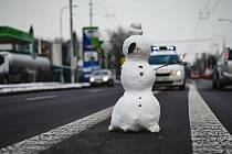 Odvážlivec mezi sněhuláky stojí uprostřed silnice.