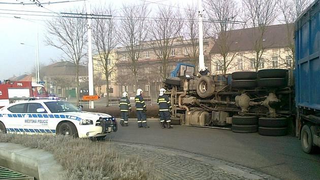 Převrácený náklaďák s odpadem na kruhovém objezdu v Lázních Bohdanči