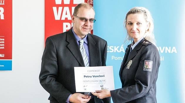 Oceněný Gentleman silnic Petr Vencl přebírá certifikát s oceněním pro Gentlemana silnic od policejní mluvčí Lenky Vilímkové. Petr Vencl se stal v pořadí sto šestým držitelem titulu za 11 let, kdy se uděluje.