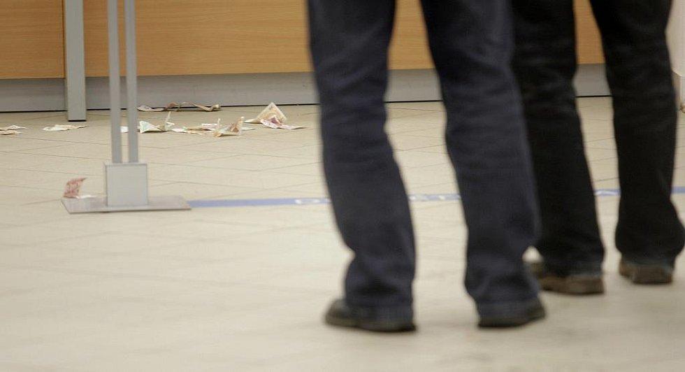 Lupič měl naspěch. Na zemi po něm zůstaly bankovky, které nestihl z pultu sebrat.