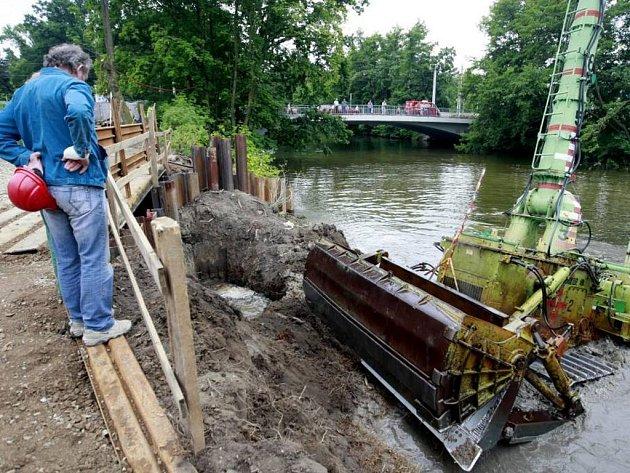 Dálkově ovládaný bagr čistí dno řeky od nánosů bahna