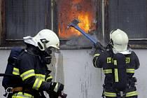 Požár skladištní haly v Černé za Bory. Hasiči museli v dýchací technice zasahovat v hustém dýmu.