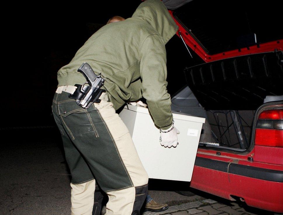 Policisté vynášejí z domu bedny plné léků a vybavení laboratoře, která je přeměňovala na pervitin