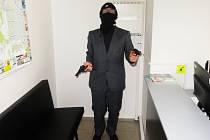 Přesně takto oblečen a šel mladý muž po ulici a mířil před sebe pistolemi. Namířil i na policejní hlídku...