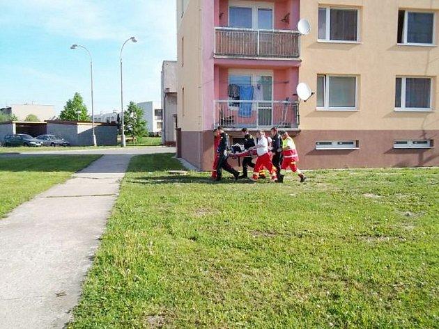 Hasiči a zdravotníci přenášejí zraněného chlapce k vrtulníku