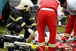 Záchranáři na místě resuscitují posádku osobního vozidla. Řidiči zaklíněnému v kabině už nebylo pomoci.