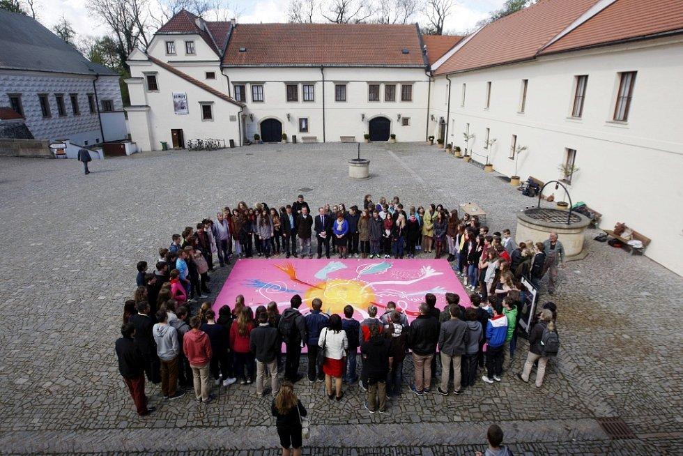 Studenti pardubického gymnázia Dašická spojili ruce nad zvětšeninou pastelu Ruce malíře Karla Malicha.