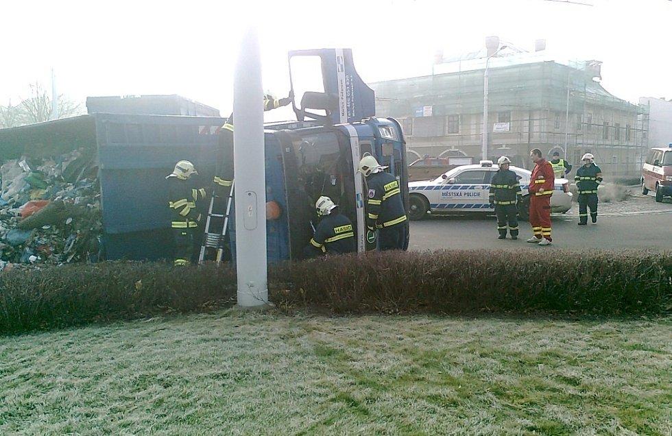 Převrácený nákladní vůz s odpadem na kruhovém objezdu v Lázních Bohdaneč.