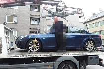 Odtahová služba naložila auto na rampu. Jeho řidič do něj pak nastoupil.