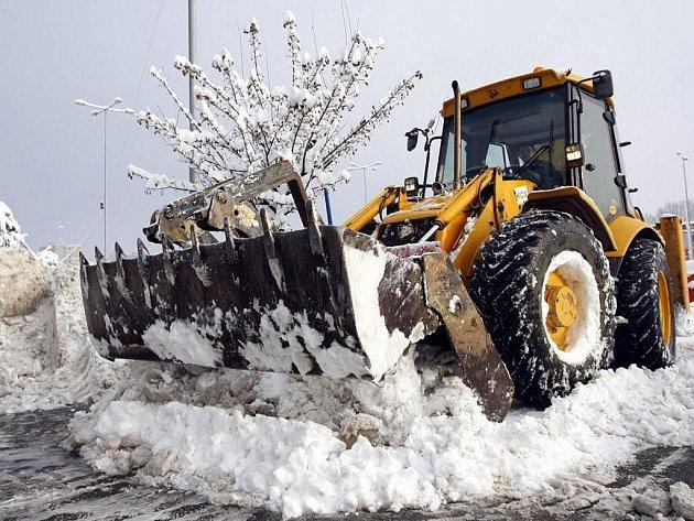 """Na odklízení sněhu nastoupili v Pardubicích i bagry. Haldy """"mokrého bílého svinstva"""" putovaly na náklaďácích do Labe."""