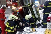 Záchranáři na místě události vyprošťují vážně zraněného muže z vozidla.