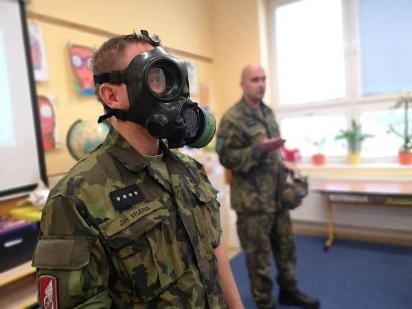 Vojáci dětem demonstrují správné nasazení ochranné masky.