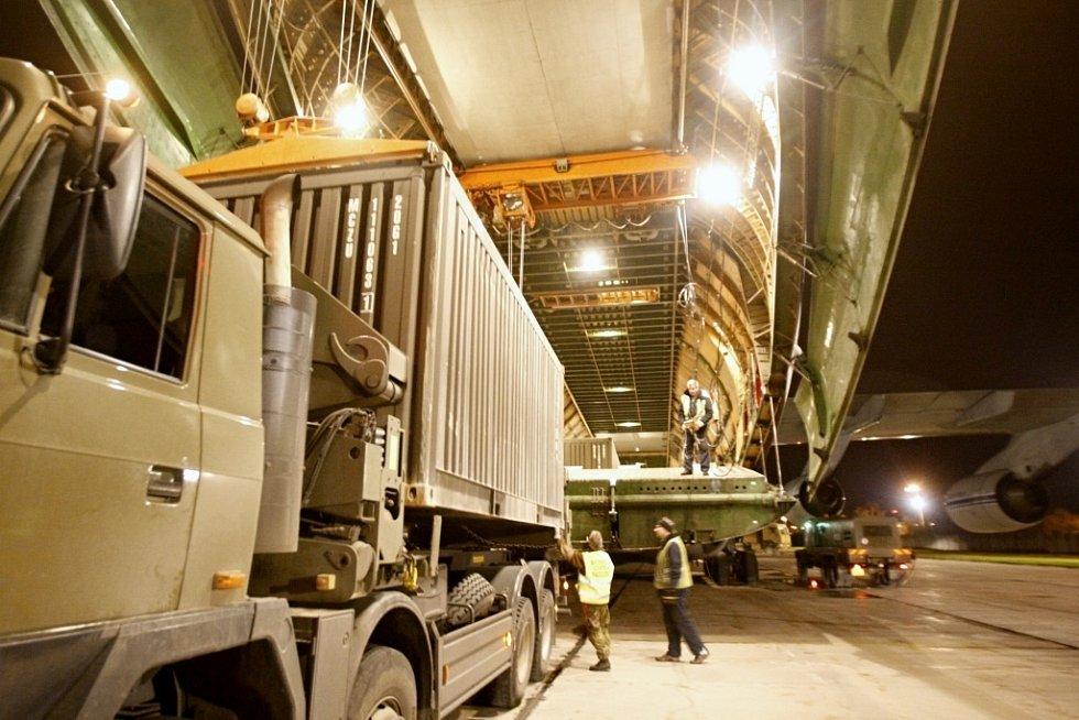 Zatímco přední částí vyjíždějí vozidla, zadní část spouští dolů kontejnery