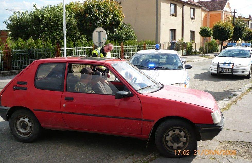 Řidič za volantem červeného vozu nejenže během jízdy popíjel vodku z láhve, ale snažil se strážníkům ujíždět