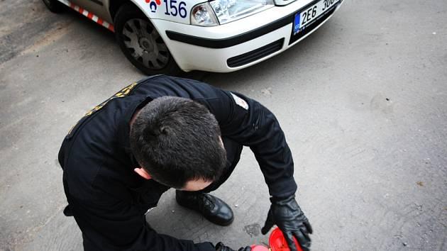 Městští strážníci odstraňují pohozenou injekční stříkačku