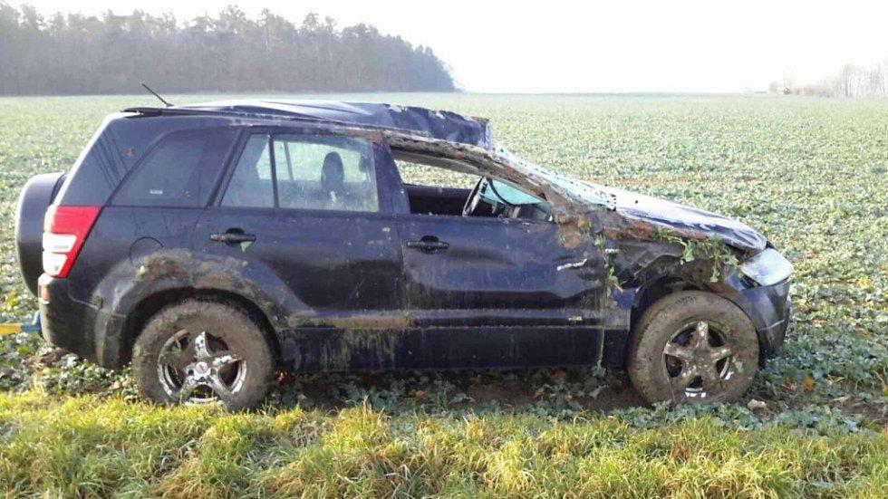 Nehoda u Chýště. Auto skončilo na boku a v poli.