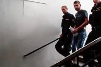 Pachatel brutálního loupežného přepadení z Trnové v doprovodu policejní eskorty na cestě do vazební věznice.