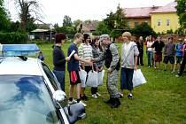 Šéf bohdanečských strážníků Pavel Řehoř odměňuje děti ze základní školy za jejich znalosti při branném dni