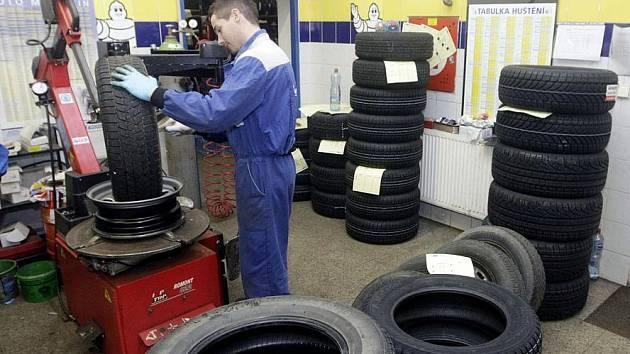 Pracovníci pneuservisu při 'přezouvání' automobilu.
