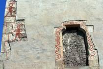 Jihozápadní nároží kostela s tajemnými postavami a českými nápisy.