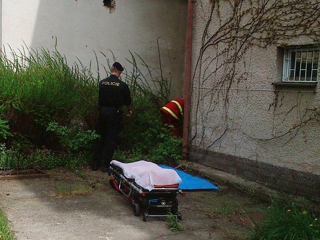 Zdravotníci a policisté krátce po příjezdu na místo události ošetřují těžce zraněného muže, který se zřítil ze střechy.