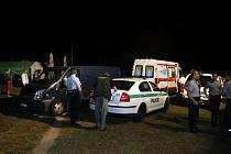 Zdravotníci překládají mrtvého sedmnáctiletého mladíka do pohřebního vozu