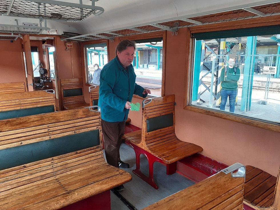 Sváteční strojvedoucí Oldřich Čížek otírá madla a sedadla pro nové cestující.