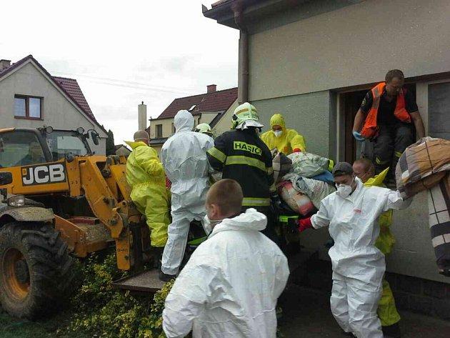 Kvůli transportu nadrozměrné pacientky museli hasiči rozebírat dům i kácet strom.
