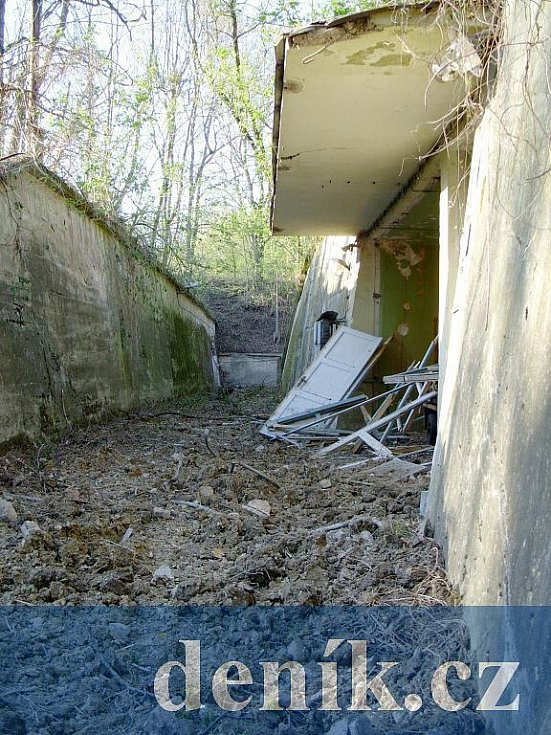 Betonový příkop, ze kterého byl přístup k budově A-55. Dveře na snímku k objetku nepatří, dostaly se na místo zřejmě následkem výbuchu.