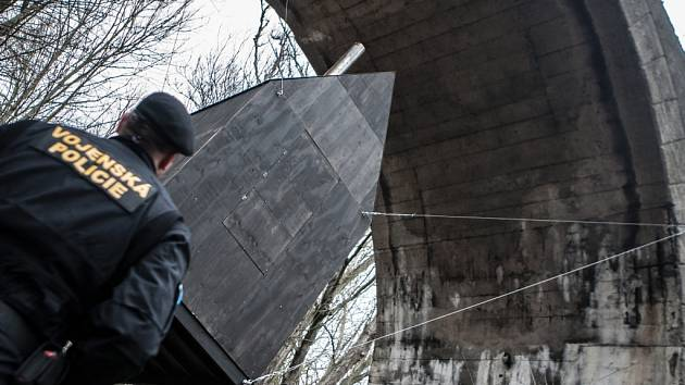 Létající černý dům zavěšený pod mostem v pardubickém vojenském prostoru Červeňák.