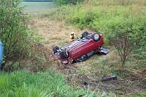 Hasiči zasahovali u nehody osobního auta. Řidič nezvládl řízení a auto skončilo za svodidly ve srázu a otočené na střeše.