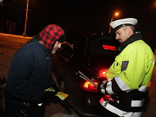 Při kontrole osvětlení jízdních kol rozdávali policisté pokuty i praktické reflexní doplňky.