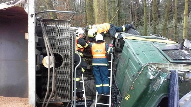 Z převráceného nákladního auta hasiči odčerpávají naftu a zároveň odklízí vysypaný písek.