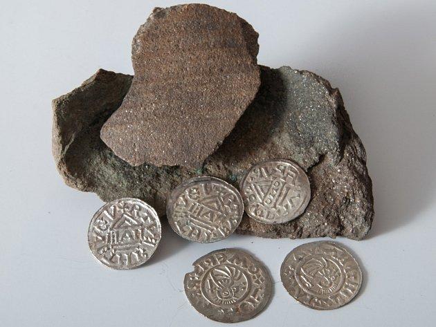 Nalezené mince z 10. století, kdy vládl Boleslav II. spolu s fragmenty nádoby, ve které byly uloženy do země.