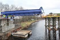 Dělníci začali s vysouváním první části ocelové konstrukce mostu přes řeku Labe, který v červenci 2020 spojí břehy Valů a Mělic.