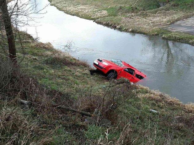 Automobil skončil ve vodě. Na břeh jej dostávali pardubičtí hasiči.