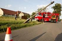 Přeražený sloup zůstal po nehodě viset nad silnicí. Odklidit ho museli hasiči.