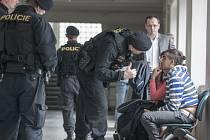 Pachatelé loupežného přepadení čekají před soudní místností na rozhodnutí o vazbě.