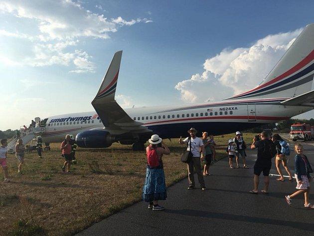 Letoun sedí asi 20 metrů za prahem dráhy. Jde o stroj společnosti Smart Wings.